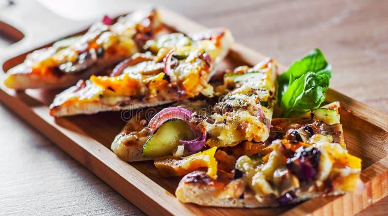 素食比萨用无盐干酪乳酪、烤夏南瓜、蘑菇、红洋葱、胡椒和新鲜的蓬蒿 在木t的意大利比萨 库存图片