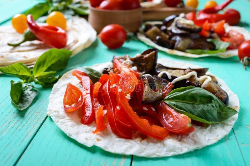 素食炸玉米饼用茄子,西红柿,在明亮的木背景的甜椒 免版税库存图片