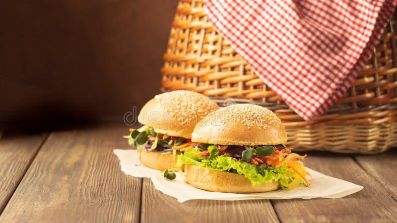 素食者汉堡由新鲜的芝麻小圆面包做了,并且未加工的蔬菜和年轻野餐射击木土气背景 图库摄影
