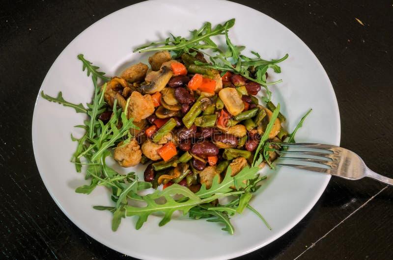 素食菜沙拉用蘑菇、芝麻菜、红萝卜、豆和胡椒 库存照片