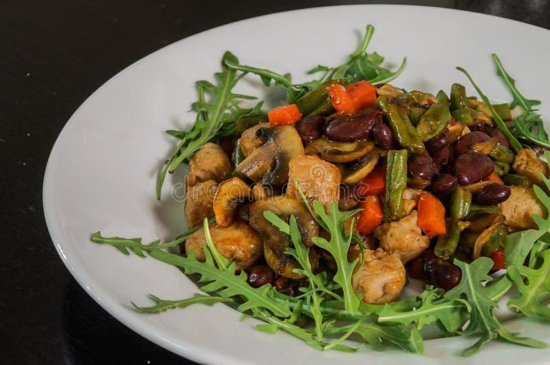 素食菜沙拉用蘑菇、芝麻菜、红萝卜、豆和胡椒 免版税图库摄影