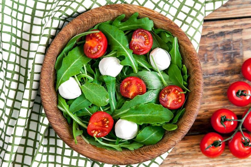 素食食物和健康概念-春天沙拉用西红柿,无盐干酪乳酪和芝麻菜在wodden滚保龄球 库存照片
