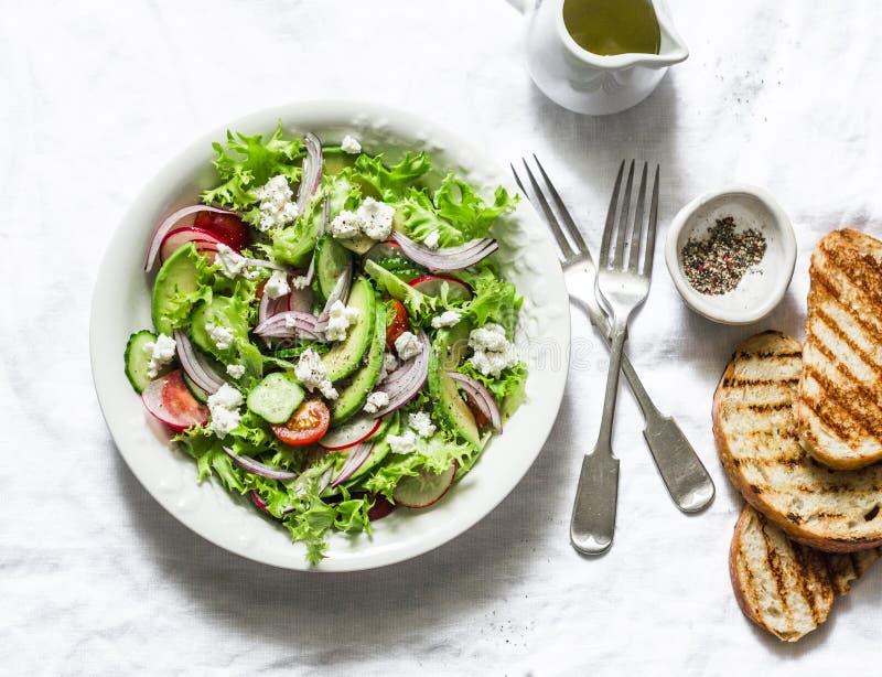 素食鲕梨、菜、希腊白软干酪沙拉和烤面包-可口健康午餐,在轻的背景的快餐,顶面 库存照片