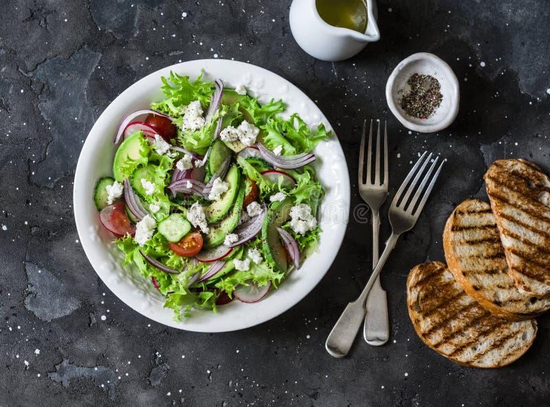 素食鲕梨、菜、希腊白软干酪沙拉和烤面包-可口健康午餐,在黑暗的背景的快餐,顶面 库存图片