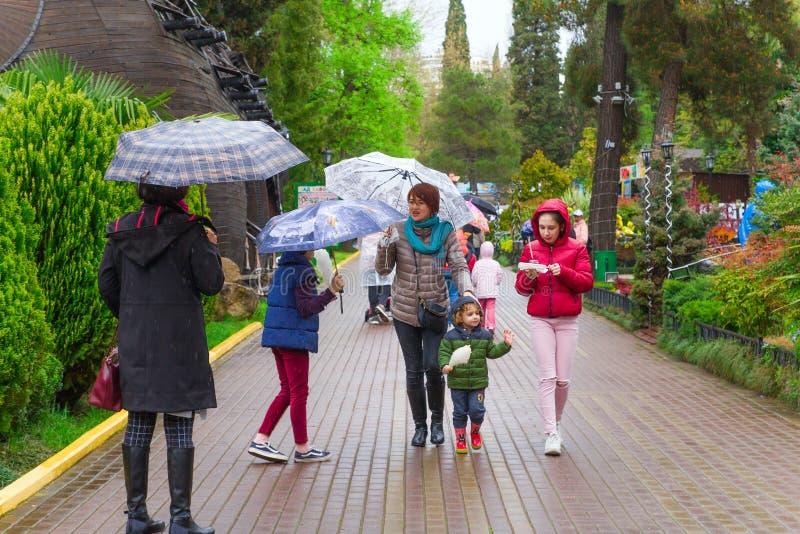 索契,俄罗斯,2019年4月21日-女性游人家庭有走在有伞的里维埃拉公园的孩子的在一下雨天 图库摄影
