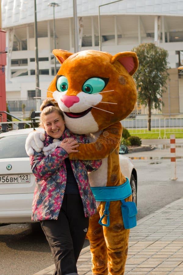 索契,俄罗斯- 2017年1月:豹子,冬奥会的标志拥抱一个女孩 库存图片