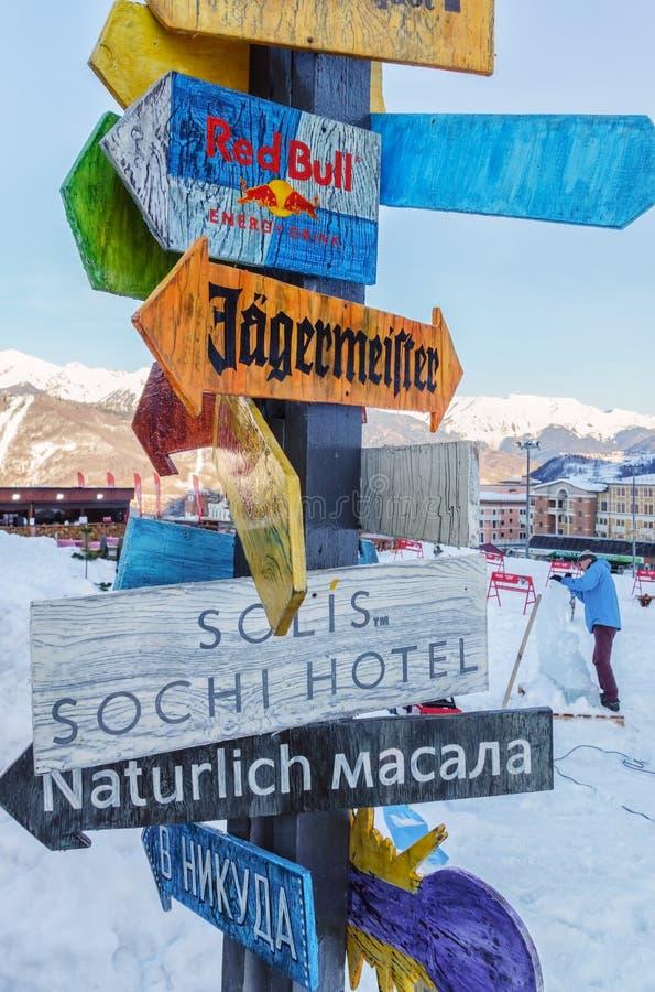 索契,俄罗斯- 2015年1月24日:室外滑雪后的咖啡馆点方向滑稽的五颜六色的木箭头板材到普遍的站点的 免版税库存图片