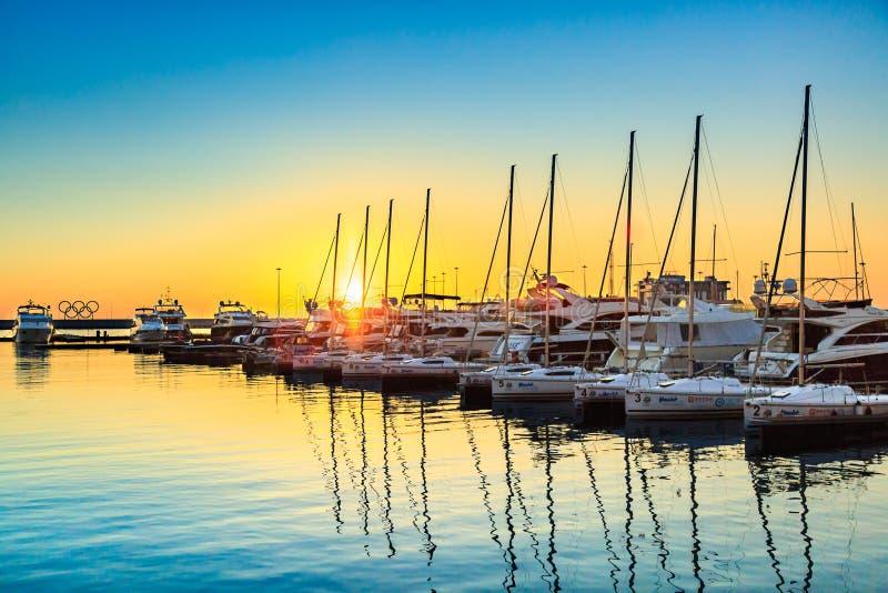 索契,俄罗斯- 2017年3月9日:风船和游艇在海港靠了码头在日落 汽艇和帆船海洋停车处  免版税库存照片