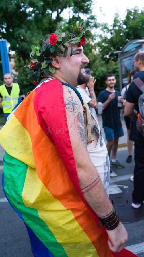 索非亚/保加利亚- 2019年6月10日:有彩虹旗子的肥胖人在花后面和冠支持索非亚自豪感走在的 免版税图库摄影