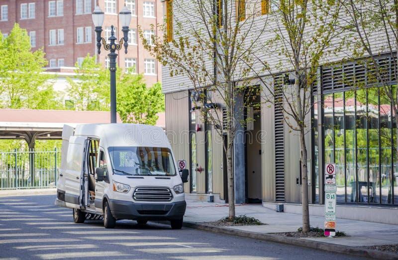 紧凑从修造在城市的multilevels的货物微型van loading货物进城 图库摄影