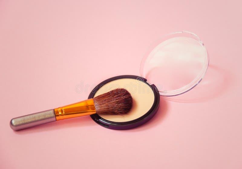 紧凑面粉和构成刷子在桃红色背景 r 免版税库存照片