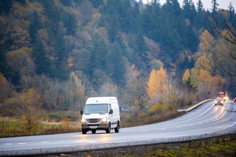 紧凑驾驶在包缠的小企业和地方交付的货物微型搬运车在雨天气的湿秋天路 免版税图库摄影