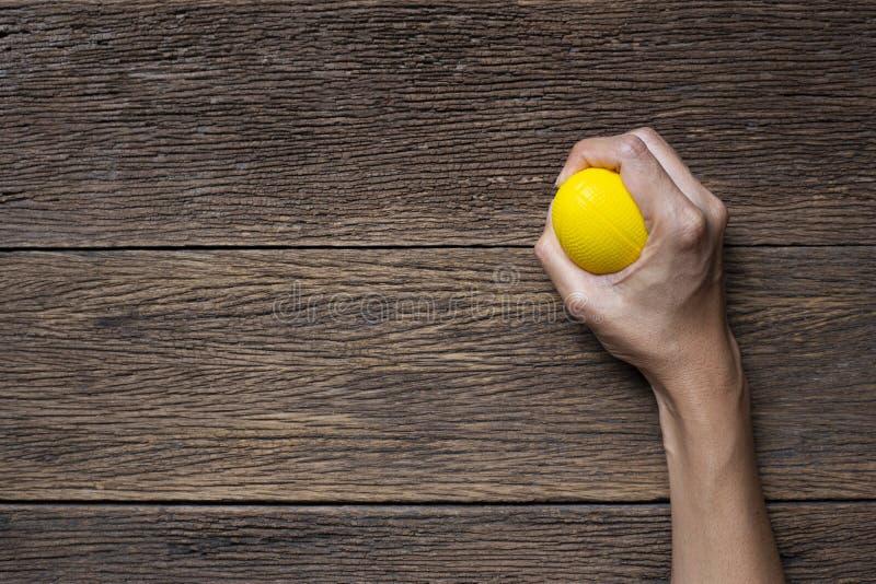 紧压在木桌背景的妇女的手一个黄色重音球 库存图片