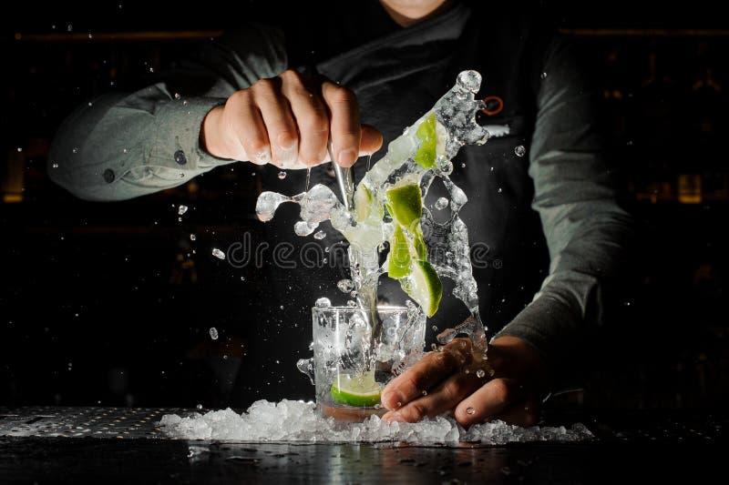 紧压新鲜的汁液的男服务员手从做Caipirinha鸡尾酒的石灰 库存照片