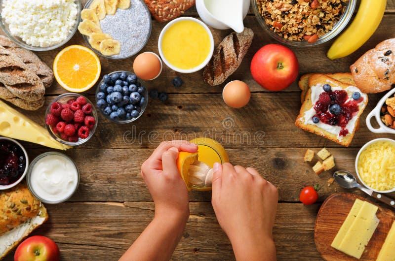 紧压橙色果子和做汁液的妇女 烹调早餐健康早餐成份,食物框架的女孩 免版税图库摄影