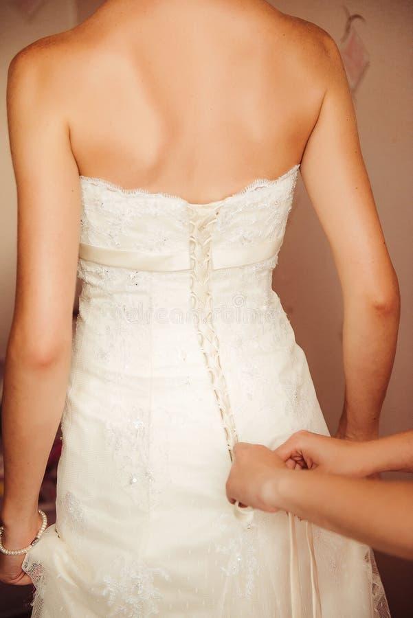 紧固在婚礼礼服的女性手按钮 库存照片