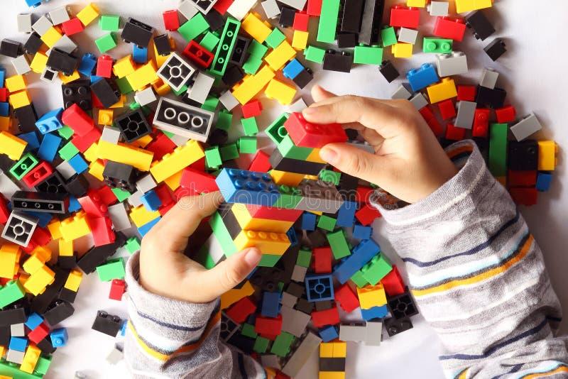 紧密从上面演奏塑料玩具积木的儿童的手,顶视图 免版税库存照片