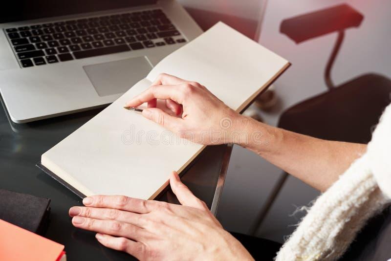 紧密做笔记的妇女的手 工作和写在纸笔记本的年轻女人或学生,使用膝上型计算机 图库摄影