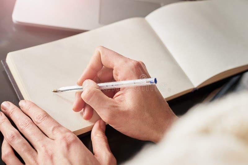 紧密做笔记的妇女的手 工作和写在纸笔记本,文本的空间的年轻女人或学生 免版税库存图片