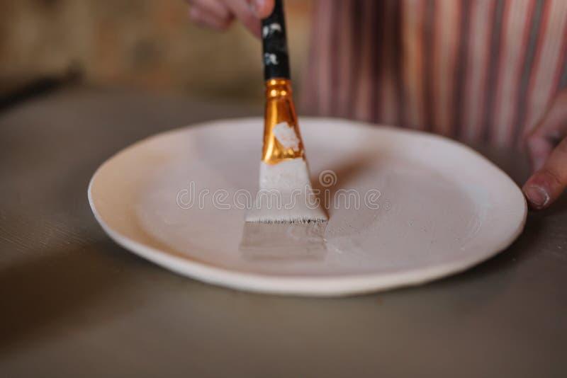 紧密做装饰品的陶瓷工的手在陶瓷产品 板材在男性手上 年轻艺术家 图库摄影