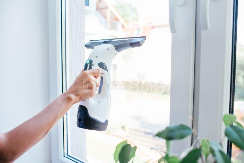 紧密妇女的手清洁与电子设备的玻璃窗 免版税图库摄影