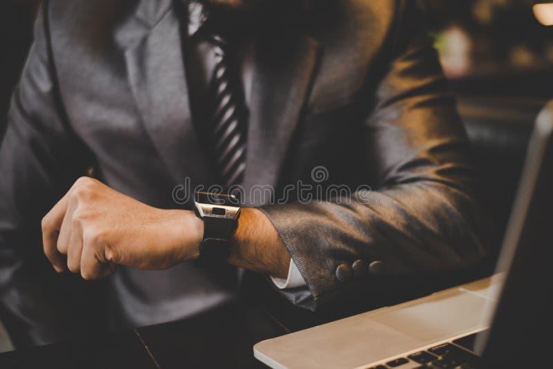 紧密看起来手头手表的商人的手 免版税库存图片