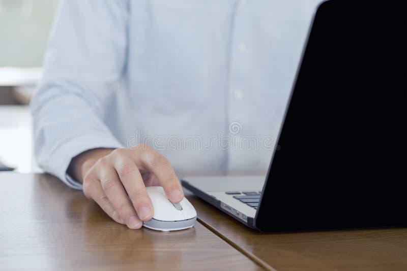 紧密,使用老鼠和计算机膝上型计算机,浏览互联网信息的商人手和搜寻网,运作外面 免版税库存图片
