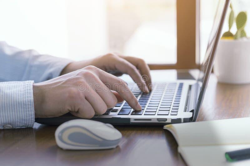 紧密,使用计算机膝上型计算机的人手,运转外面 库存图片