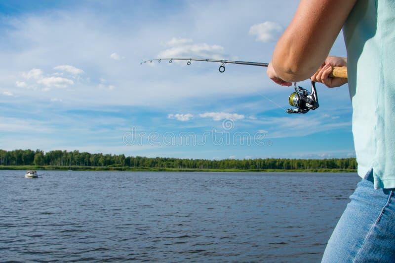 紧密,钓鱼在转动,反对天空蔚蓝和湖,有题字的地方 免版税库存照片