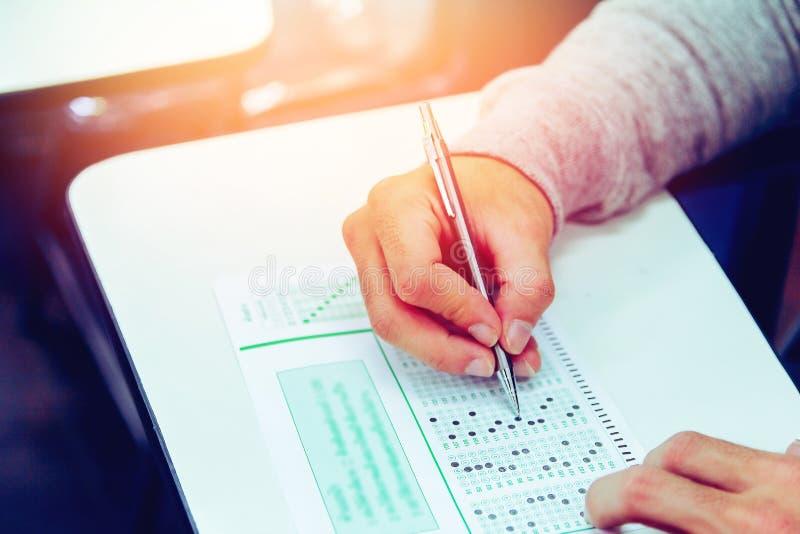 紧密,高中男生藏品写在教室的铅笔检查为教育测试,复制您的文本的空间 免版税图库摄影