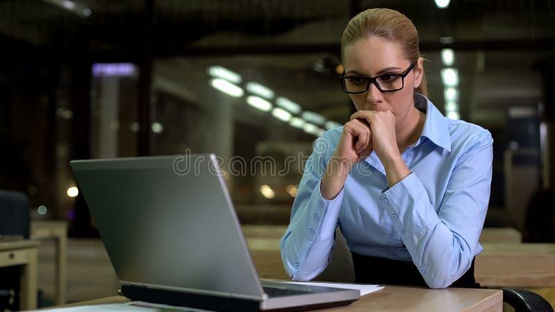 紧张女商人看膝上型计算机的,害怕工作失败和坏消息 免版税库存照片