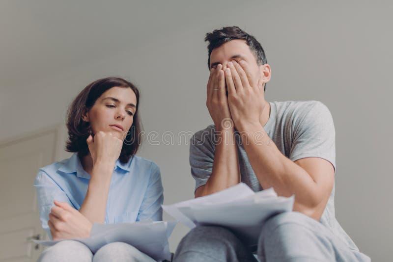 紧张家庭夫妇有债务问题,不能支付他们的贷款,处理国内预算,研究纸张文件,姿势 免版税图库摄影