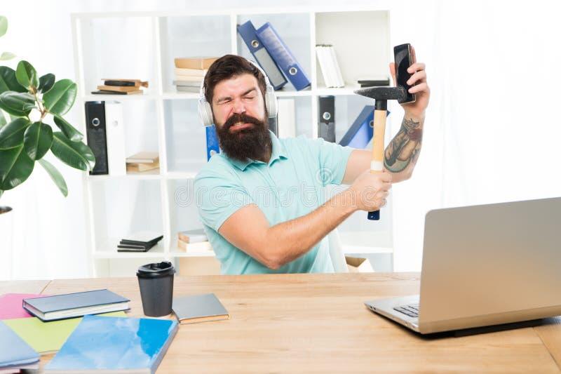 紧张工作在电话中心 人有胡子的人耳机办公室锤子智能手机 被损坏的通信 不合格的机动性 免版税库存图片
