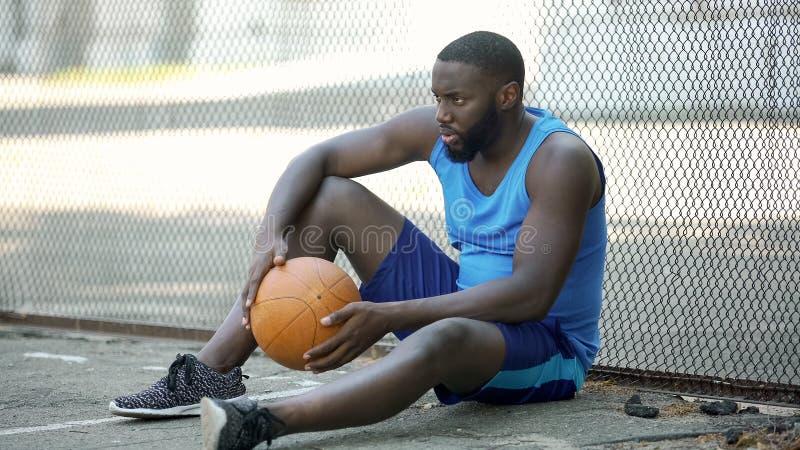 紧张的人在运动服坐的单独近的体育场和举行球,失败者内 库存照片