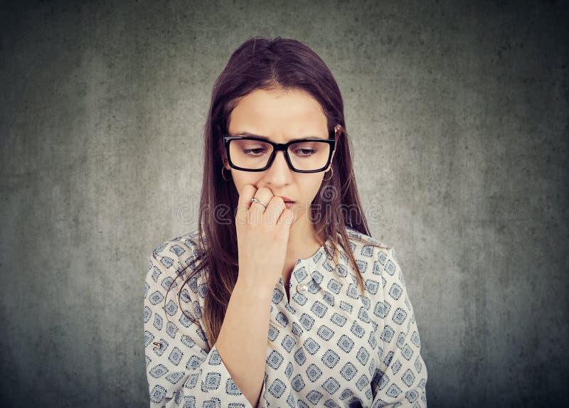 紧张的妇女尖酸的钉子和看下来 免版税库存照片