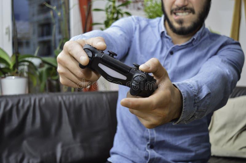 紧张的年轻帅哥藏品比赛垫和播放对电子游戏 免版税库存图片