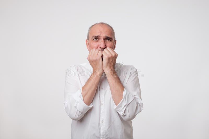紧张的窘迫人咬住钉子 成熟商人神色在拜访医生或牙医前担心 图库摄影