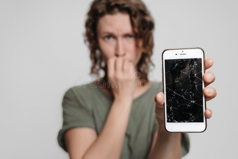 紧张的窘迫女孩叮咬钉子,拿着她残破的智能手机 免版税库存图片