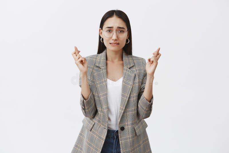 紧张的采访的女孩等待的结果,祝愿得到工作 玻璃的悦目成年女性企业家 免版税库存图片