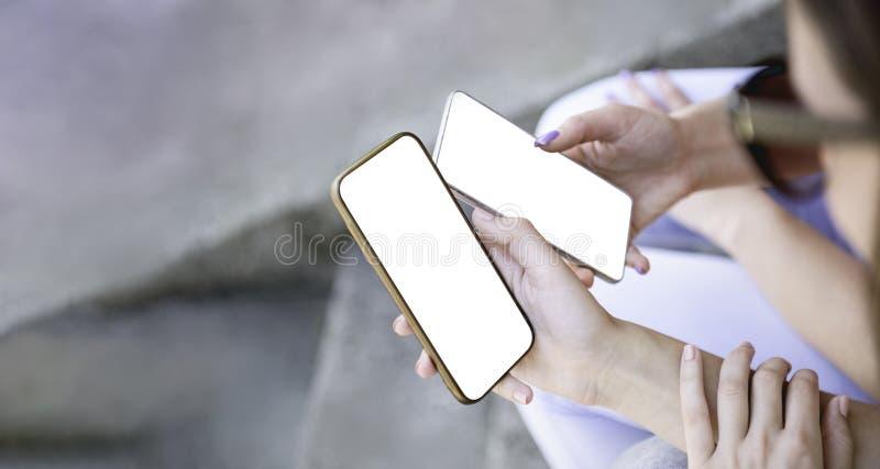 紧挨着拿着流动智能手机的两个女孩分享大模型白色屏幕背景剪报使用智能手机空白 免版税库存照片