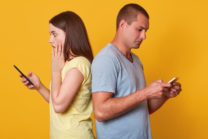 紧接站立对人的震惊情感妇女,接触她的面颊用手,拿着手机,看它的屏幕, 库存照片