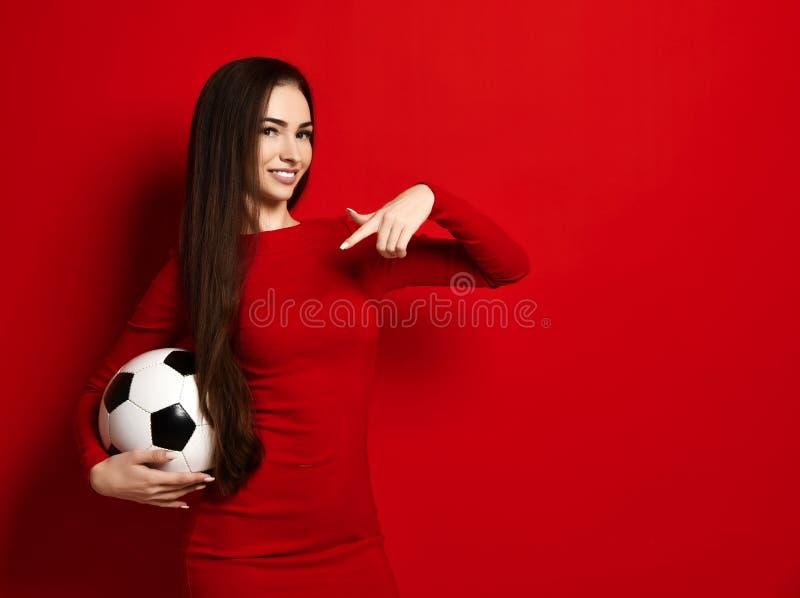 紧的红色礼服的俏丽的踌躇满志的微笑的深色的妇女拿着足球并且把她的手指指向它 库存图片