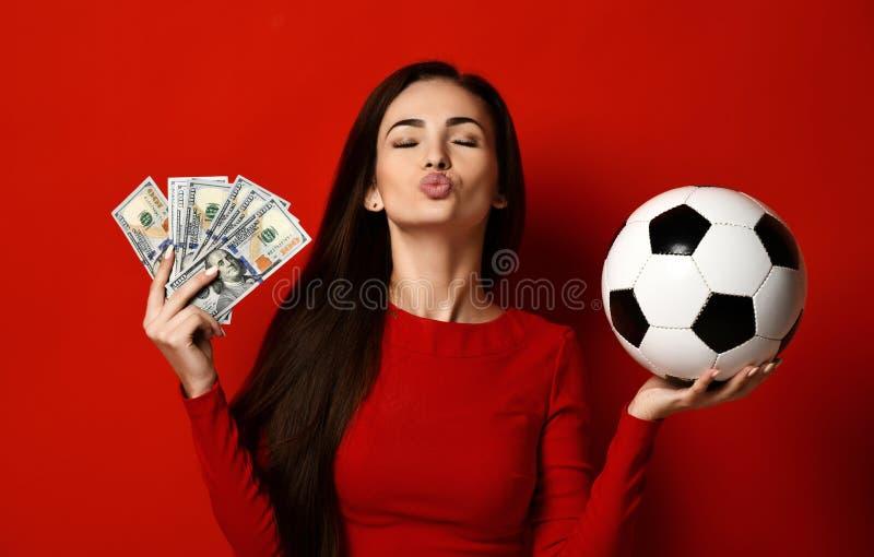 紧的红色礼服的美丽的深色的妇女拿着足球baland捆绑美元并且送亲吻 库存照片