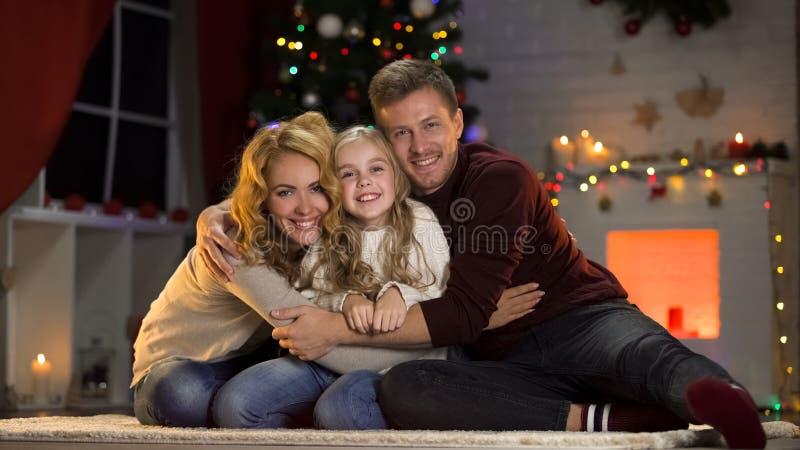 紧紧拥抱喜爱的女儿的父母在圣诞树,统一性下 库存照片