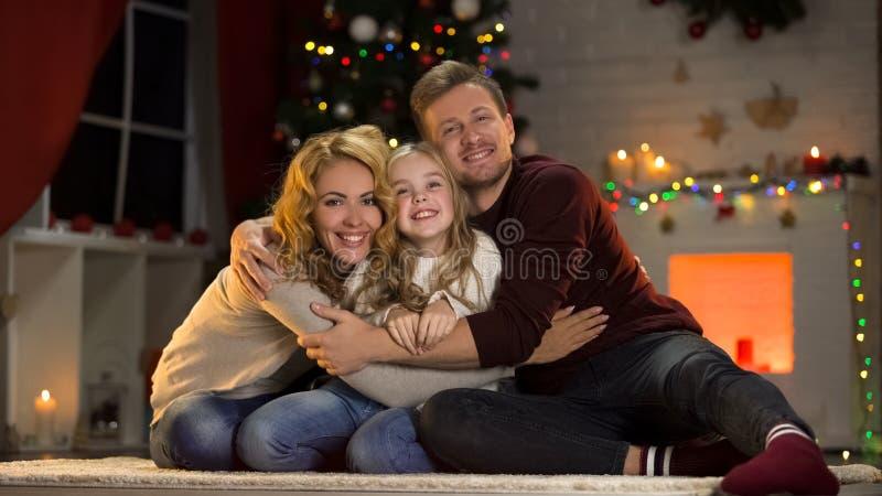 紧紧拥抱女儿的愉快的父母在圣诞树,统一性下 免版税图库摄影