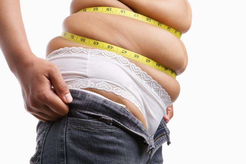 紧紧肥胖牛仔裤端对尝试的穿戴妇女 免版税图库摄影
