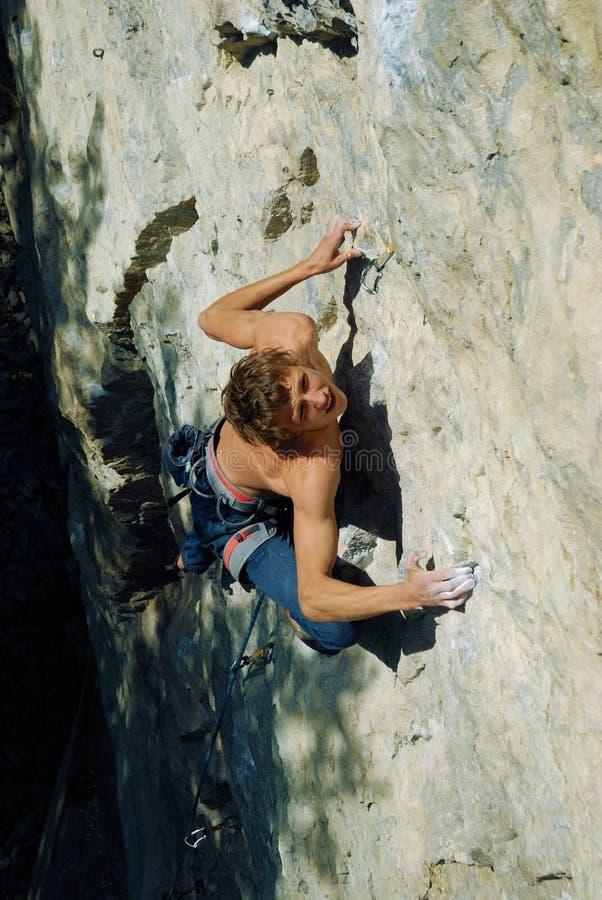紧贴对峭壁的年轻攀岩运动员 免版税库存图片