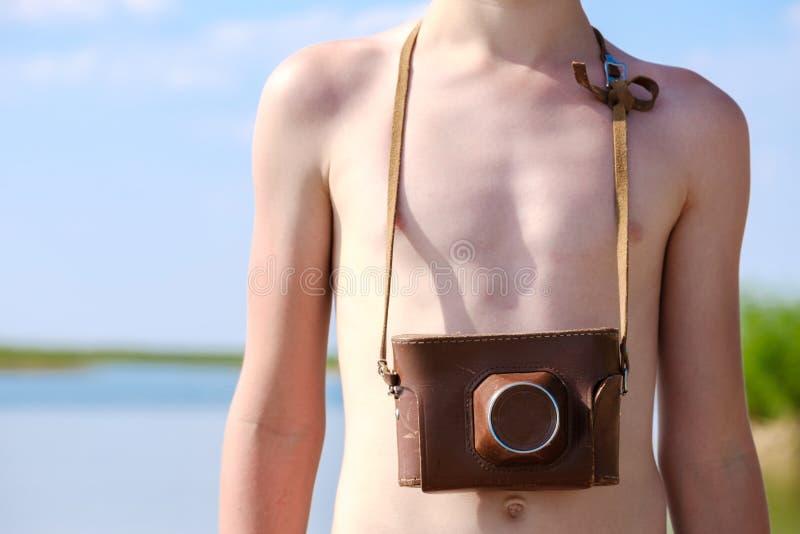 紧跟在少年后面垂悬在皮革盖子、夏日海滩和太阳的一台照相机 免版税库存照片