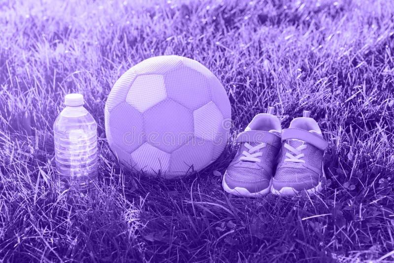 紫外女孩运动鞋鞋子、儿童织品软的足球和瓶在外面草的水 免版税图库摄影