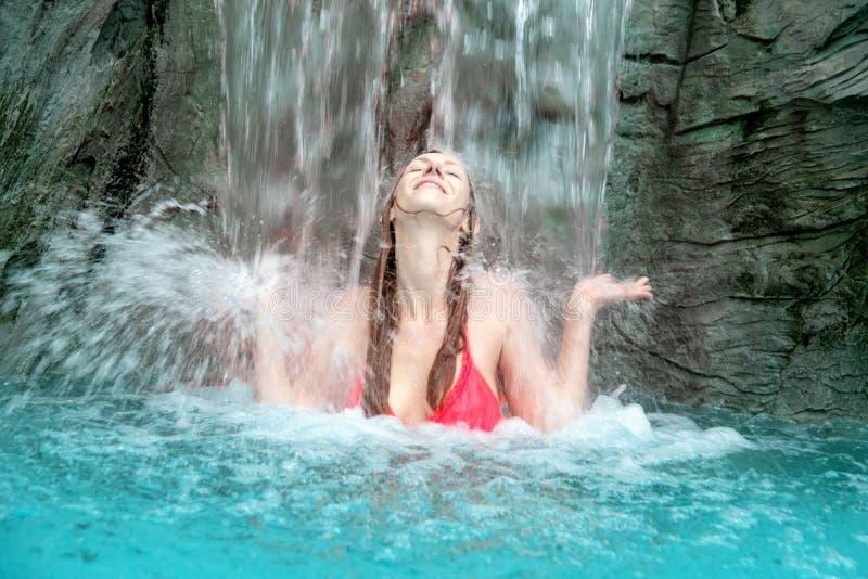 紫红色的比基尼泳装的年轻性感的白肤金发的妇女举她的手反对瀑布的飞溅的水 库存图片
